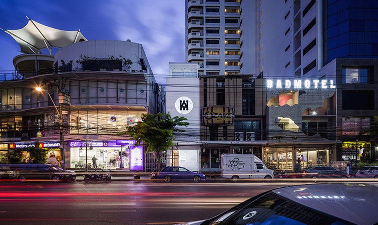如果你是个对食物和运动鞋拥有同样热情的人,在泰国曼谷有这样一家名为「Knock Kitchen & Kicks」的集合店,或许值得你在那里浪费一个下午。 曼谷的通罗区(Thonglor)长久以来被视为曼谷的潮流圣地,这里有大量的餐厅、酒吧、夜生活节目和社区购物中心,Knock Kitchen & Kicks 恰好就选址在这里。他们请来了当地知名的建筑设计事务所 Onion 操刀内饰设计。 色彩成为整个空间设计的主线。入口处是经典的黑白灰混搭,但并无冰冷的感觉。踏上纯黑色调的台阶,左边是一面