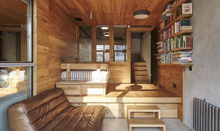 住宅最大的特征是一些区域被抬高了,比如整个起居室和卧室的一部分。抬高的地方并不是水泥地面,而是增加了一层木材,与地面形成了的空隙就作为抽屉。据计算,住宅里的抽屉多达 57 个,加上两个衣橱和食物储藏柜就不再需要任何储物空间。这就为室内腾出了不少空间,不会因为增加柜子而打破原本风格或是显得拥挤。 被抬高的客厅在前半部分的正中间,它作为一个家庭中沟通交流的枢纽。客厅旁有一个适合儿童的看书的角落,柜子的中间被切断,构成一个看书的桌面,上面的吊柜可供大人使用或者利用移动楼梯拿取,橡木做的地板、天花板、书柜和