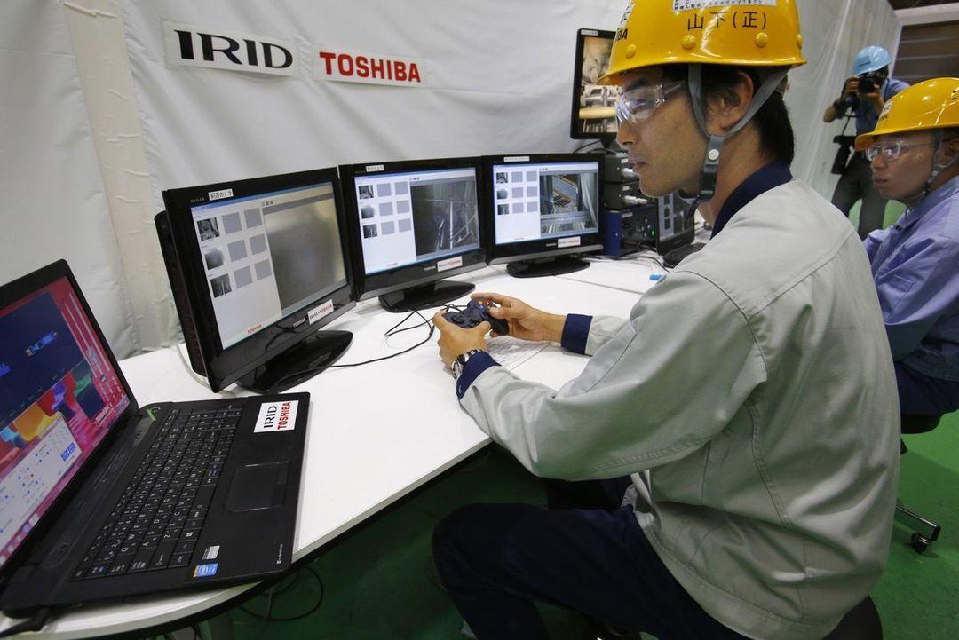 工人似乎在用索尼 PlayStation 的游戏手柄在操控