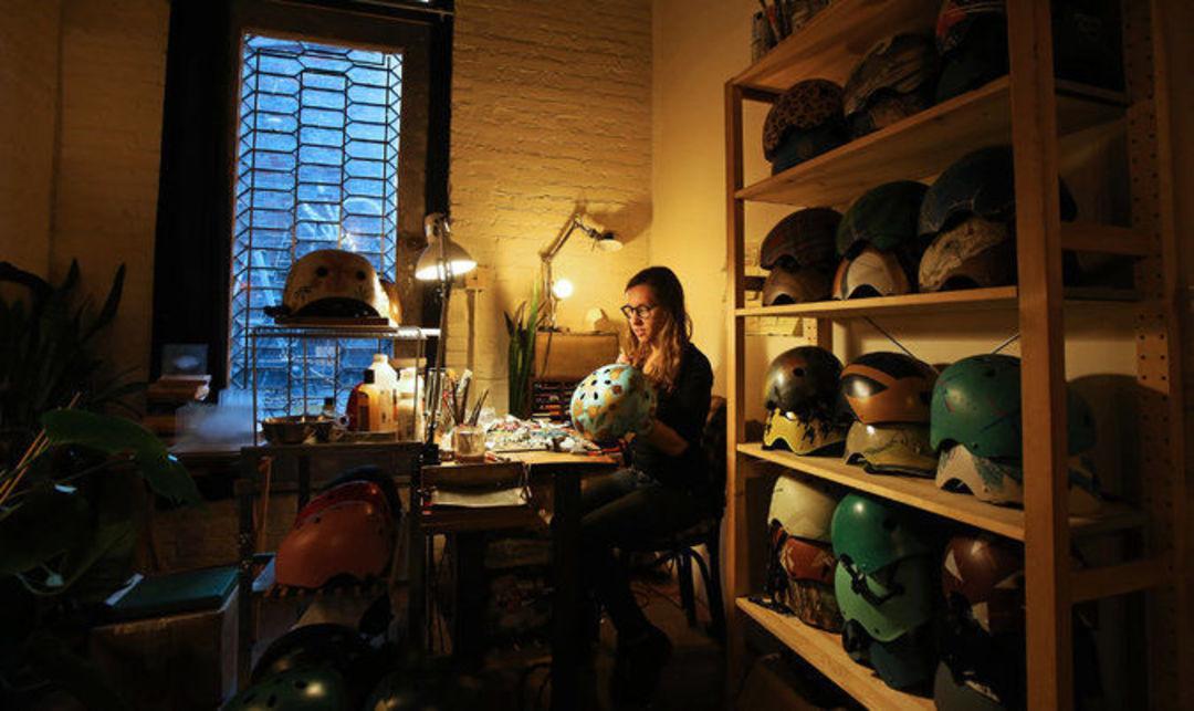 丹妮尔·巴斯金正在她位于纽约东村的工作室里绘制自行车头盔。这间工作室是她名下六家公司中的一家的办公地。图片来源:Nicole Bengiveno / 《纽约时报》